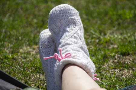 Female feet in a beautiful socks on the nature