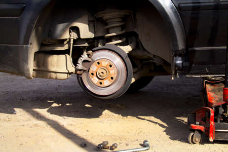 Wheel replacement on black sedan car, jack holds the body in the raised position