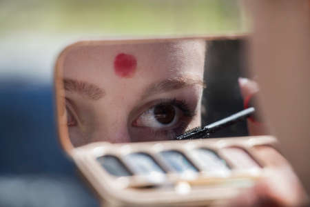 mirror: The girl corrects eyelashes in mirror