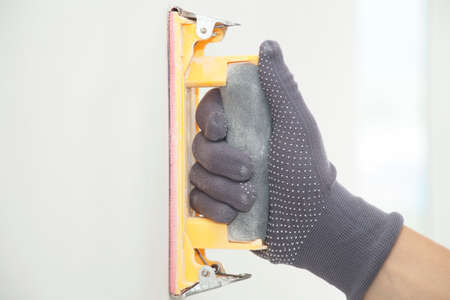 hand grinding with sandpaper on a white wall