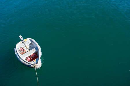 Single boat floating on blue-green sea