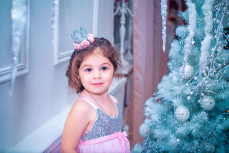 5 years old: 5 years old little girl dressed in beautiful fashion white flower dress posing near Christmas tree