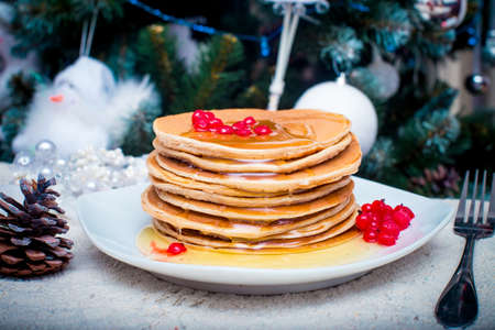 flapjacks: Stack of fresh golden pancakes or flapjacks topped with fresh autumn berries and drizzled with honey or syrup and white sugar