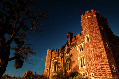 LONDON, circa 2016 - Dramatic shot of the facade of the Hampton Court Palace with the Union Jack in London, England, UK during sunset Editorial