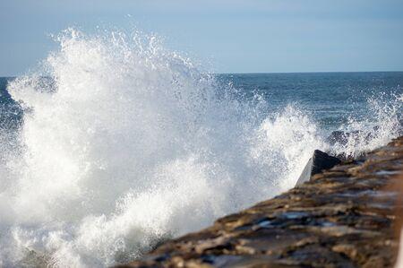 sea water splashing on the breakwater of san sebastian in Spain
