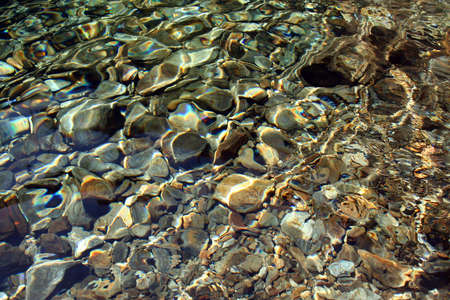 Background of river rocks, with some light efects on the water. Stock Photo