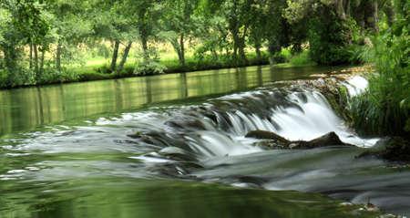 Une chute d'eau � proximit� d'un lac calme entour� d'arbres.
