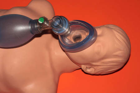 A dummy recieving CPR on a red background. photo