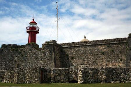A lighthouse under a cloudy sky.
