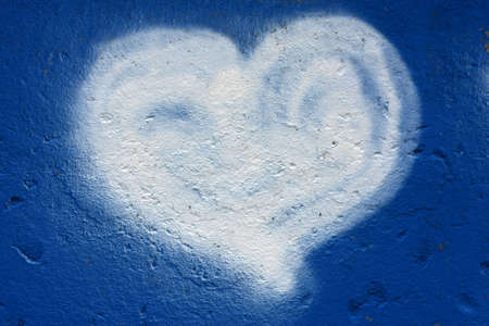 A grafity of a heart on a blue wall.