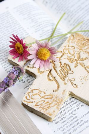 Bible opened at a piece of scripture with a cross and flowers photo