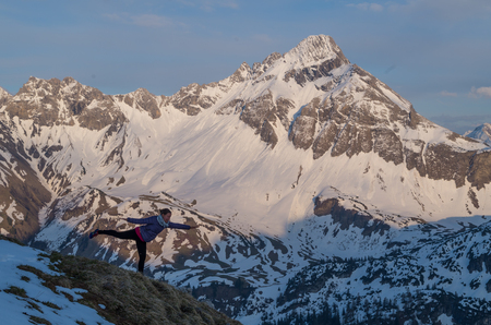 allgau: Female in yoga posture in the mountains in Allgau during sunset, Germany Stock Photo
