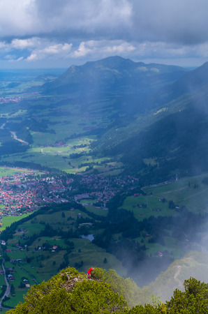 townscape: Female mountaineering in the Allgau mountains with townscape of Oberstdorf in the background, Germany