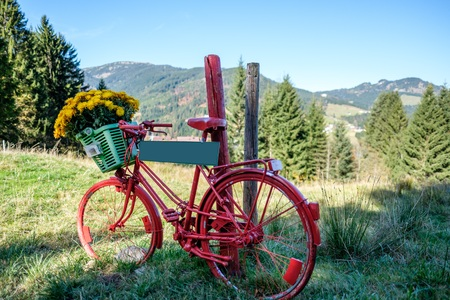 Retro red bike with flowers and a sign in front of a mountain landscape Фото со стока