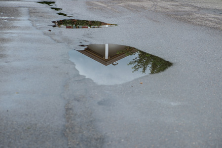 Reflection of a house in a water puddle after a rain storm