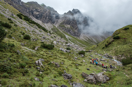 Large group of hikers in the allgaeu alps near Oberstdorf on a cloudy day