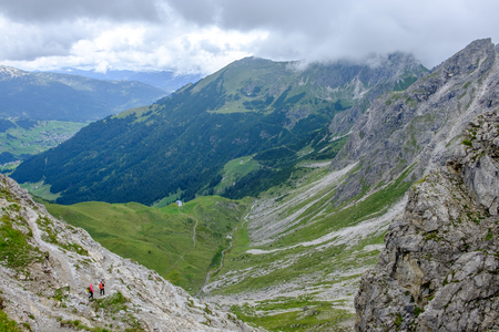 Two hikers descending into a valley in the Allgaeu moutains on a cloudy day, Austria Фото со стока