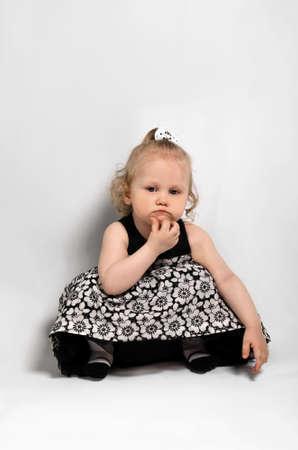 decides: little girl in a beautiful dress studio photo
