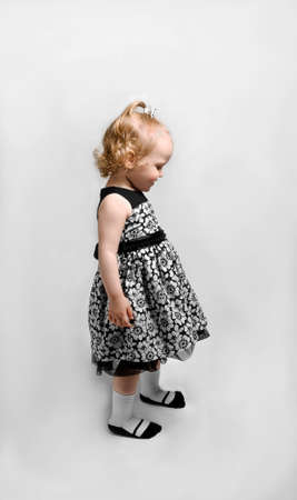 multilayered: Girl in black and white dress stands and looks down into the profile