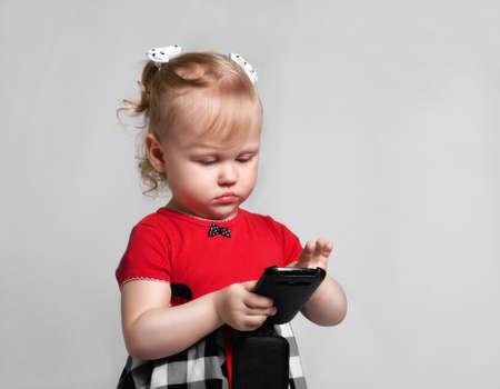 preteen model: little girl with smartphone look screet photo studio