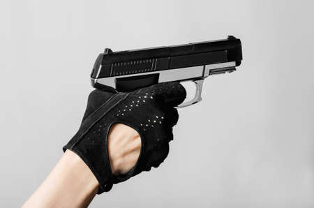 finger on trigger: Female hand with a pistol in a black glove aim and pulled the trigger Stock Photo