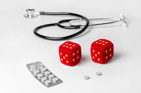 heed: Stethoscope pills and dice on a white table
