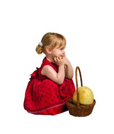 Little girl in a red satin velvet dress sitting next to a basket, which is a big delicious yellow melon