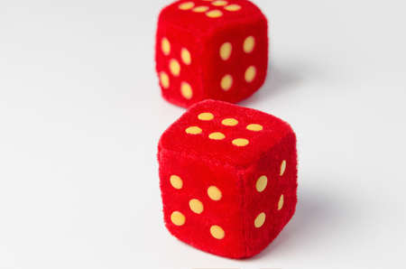 red dice: toy soft red dice on white table closeup two sixes