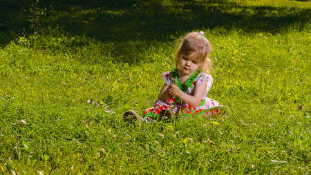 lost in thought: Little girl age of three years, sitting on the lawn lit by the sun and holding a dandelion