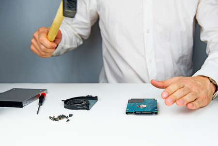disassemble: The man with the hammer swings on the hard drive to the laptop to break it on the table to disassemble the laptop