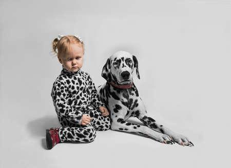 alike: Little girl sitting near the Dalmatian dog