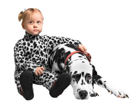 Little girl sitting near the Dalmatian dog and embraces it with one hand