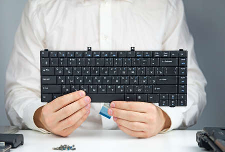 man in a white robe sitting at a table with a laptop and dismantled holds a Laptop Keyboard Stock Photo