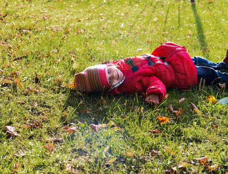 he laughs: Little girl in a red jacket lying on the ground in the sunshine and laughs Stock Photo