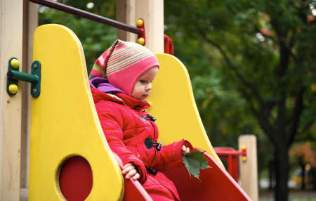 Girl in a red jacket rides on a hill at the playground Stock Photo