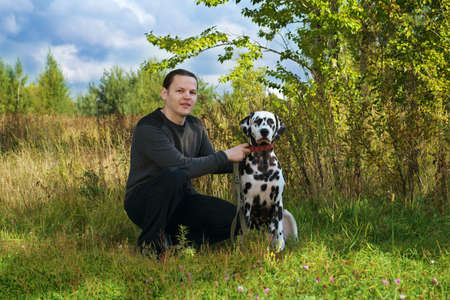 spotted dog: owner man sitting outdoors with a black and white spotted dalmatian dog photo