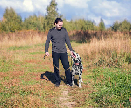 he laughs: young man walking a dog Dalmatian outdoors in the park green Stock Photo