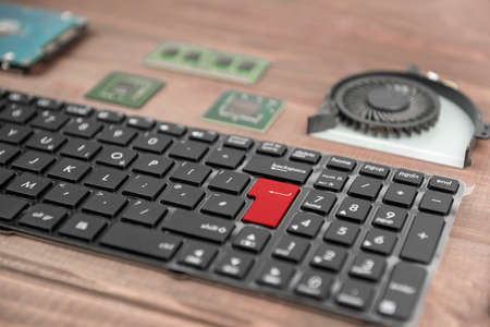 hard component: The keyboard for laptop on a wooden table close-up on a background component. The chip, hard drive and fan.