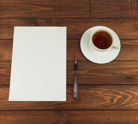 your text: White paper on a wooden table next to a cup of tea, and ballpoint pen - Business concept with space for Your text and picture Stock Photo
