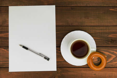 your text: White paper on a wooden table next to a cup of tea, bagels and ballpoint pen - concept with space for Your text and picture