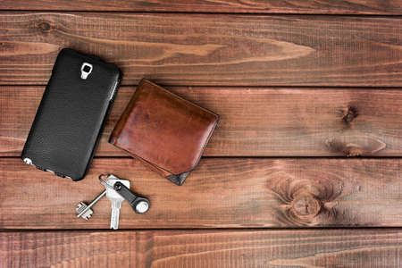 house top: Leather purse, phone pouch and keys on a wooden table background. Required items for the man at the exit of the house that can not be forgotten.