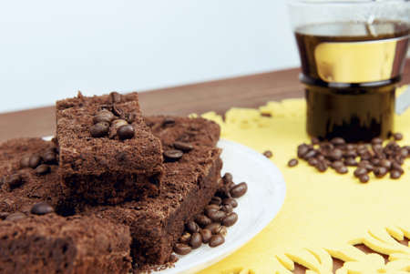 caterers: On a wooden table on yellow napkin glass cup of coffee with a spoon and a plate of chocolate truffle cake, a lot of coffee beans - small DoF focus put only to pier