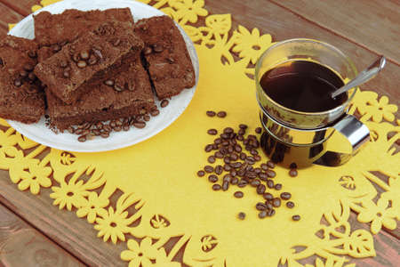 caterers: On a wooden table on yellow napkin glass cup of coffee with a spoon and a plate of chocolate truffle cake, a lot of coffee beans