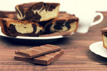 carte: Marble cake in white plate cut into pieces a la carte, standing next to a cup of hot chocolate and milk chocolate tile pieces on a wooden table in the rural-rustic style Stock Photo