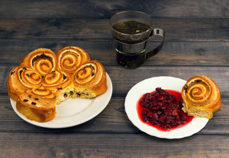 fancy cake: On a wooden table white plate with a nice fancy cake and a glass cup with green tea leaf grass, near a saucer with