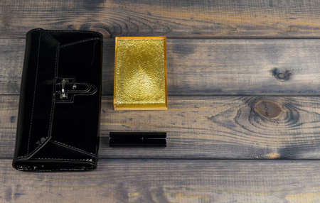 Purse-clutch black, powder box with mirror and lipstick golden lie on a wooden table background, there is a place for your text or image