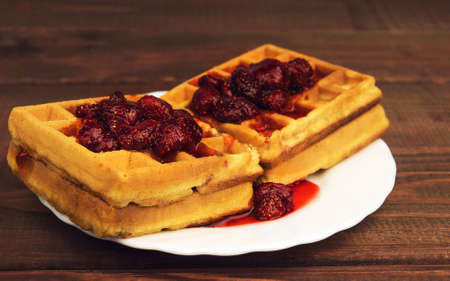 watered: Soft homemade waffles on a wooden table background poured on top of a red berry strawberry jam - a place for your text or image