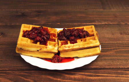 watered: Soft homemade waffles on a wooden table background poured on top of a red berry strawberry jam Stock Photo