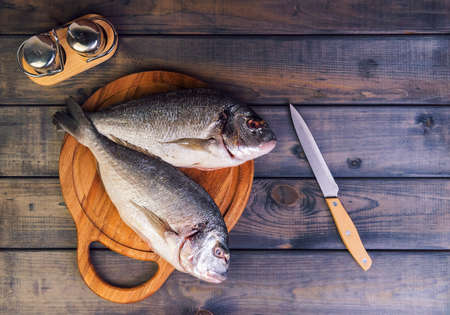 gutted: n a wooden table cutting board with fresh raw dorado fish gutted, near the knife, salt and pepper - top view Stock Photo