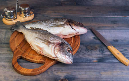 gutted: n a wooden table cutting board with fresh raw dorado fish gutted, near the knife, salt and pepper